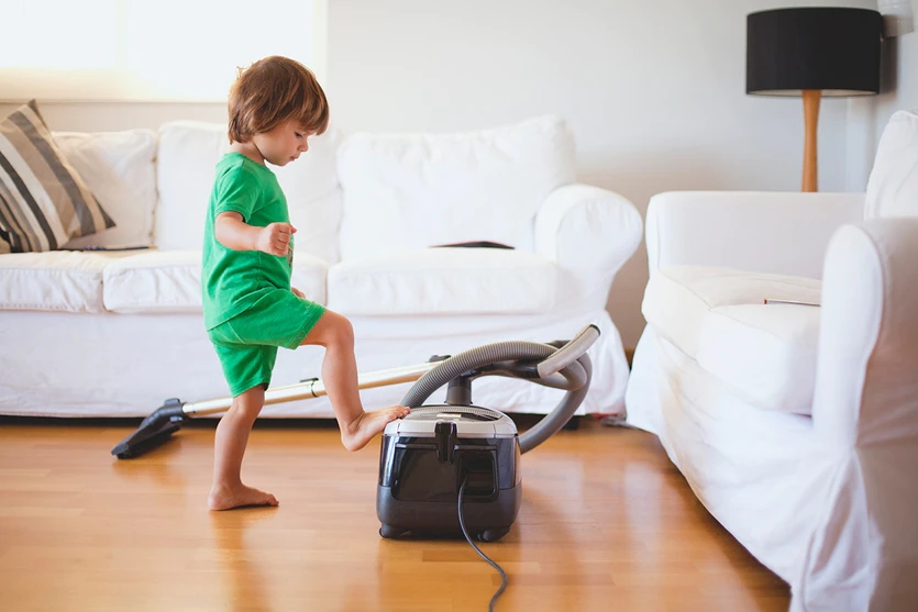 kid playing with vacuum cleaner